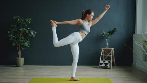 Flexible girl doing balancing asana during individual practice in sports center Live Action