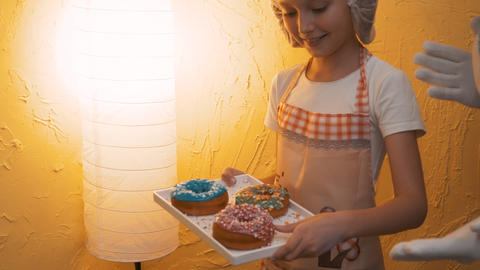 Young cook girl holding tray with colorful glazed donuts. Happy girl cook in Live Action