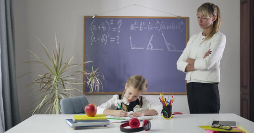 Strict Caucasian teacher looking at schoolgirl drawing in exercise book Live Action