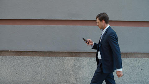 Side view business man walking with phone. Man using phone near modern building ライブ動画