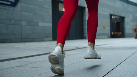 Close up female legs jogging on urban street. Athlete woman legs running outdoor Live Action