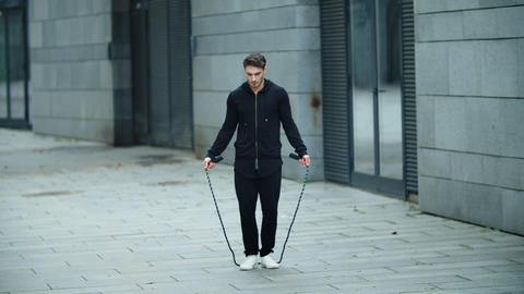 Sportsman training jump exercise on skipping rope. Athletic man jumping outdoor Live Action