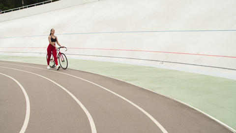 Woman walking with bicycle at track. Girl resting after workout on velodrome Live Action