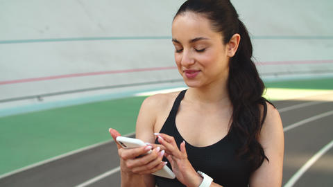 Portrait of sport woman using phone at stadium. Fitness woman looking smartphone Live Action