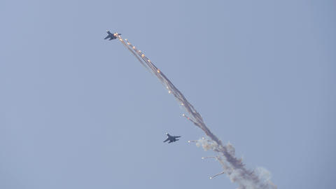 Supersonic planes in the blue sky perform aerobatics. The plane releases Live Action