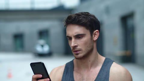 Closeup athlete man looking smartphone on street. Smiling man reading message Live Action