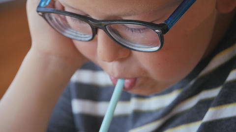 Little boy drinks a milkshake through a straw. Child blows through a tube and Live Action