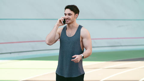 Sport man call mobile phone standing on track outdoor. Fitness man talking phone Live Action