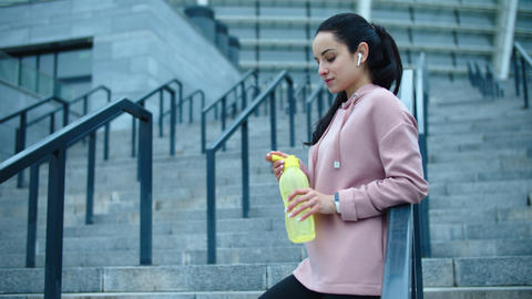 Athlete woman drinking water in slow motion. Thirsty woman relaxing on staircase Live Action