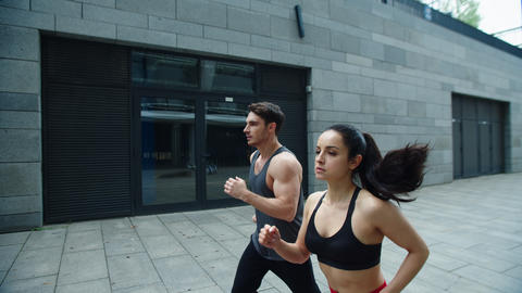 Sporty couple running outdoor together. Young man and woman training run outdoor Live Action