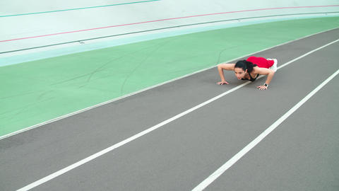 Fitness woman doing push ups on track. Sporty girl doing pushups exercise Live Action