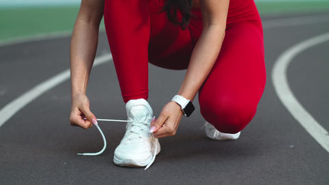 Close up of fitness woman lacing up footwear for marathon on track Live Action