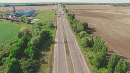 Flight over village fields, grain silos storage road. Countryside aerial 4k vido Footage