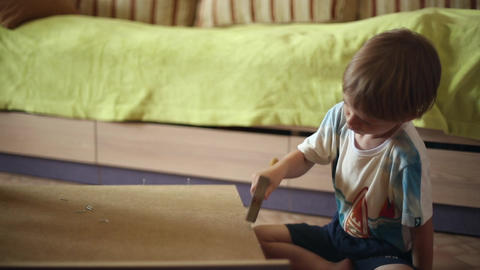 The boy is hammering nails with a hammer Stock Video Footage