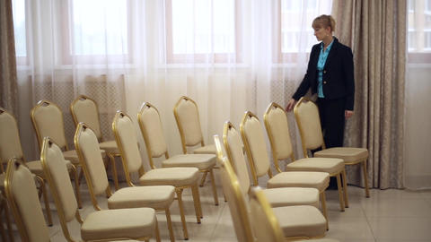Girl secretary moves the chairs in the conference room Footage