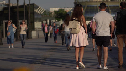 Group of friends walk together on sunlight promenade, slow motion Footage
