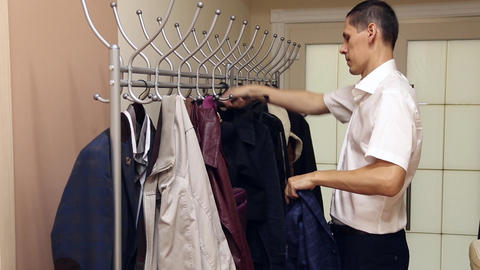 A man is hangng the jacket on a hanger Footage