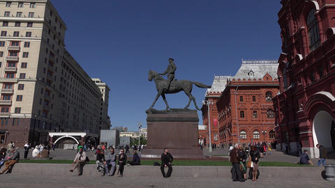 People sit around Marshal Zhukov monument near Historical Museum, tracking shot Footage