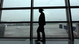 Businessman with briefcase confidently go at airport airside against glass wall Footage