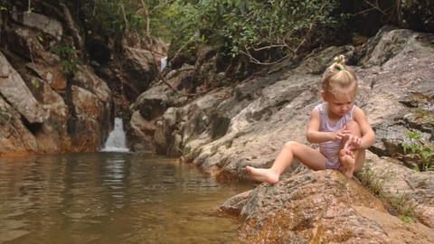 Little Blond Girl Sits Cleans Foot on Stone by Waterfall Footage