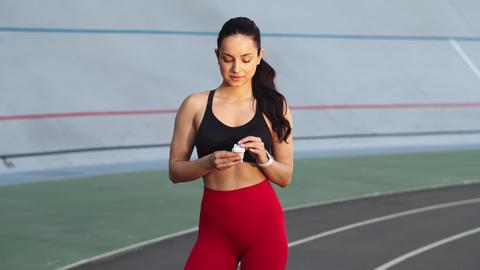 Sexy woman listening music in wireless headset. Sport woman wearing earphones Live Action