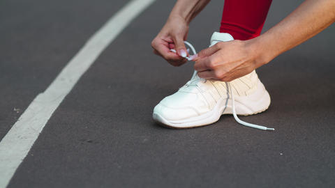 Closeup woman lacing up sneakers on track. Fitness girl lacing up shoes Live Action