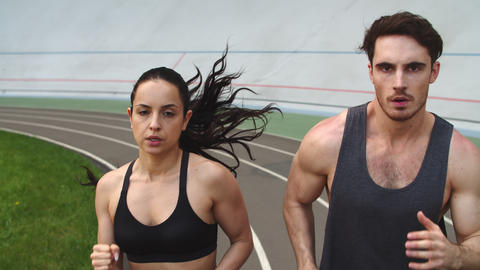 Portrait of sporty couple running at sport stadium. Fit man and woman sprinting Live Action