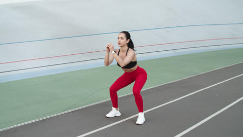 Fitness girl doing squat exercises on racetrack. Sporty woman exercising Live Action