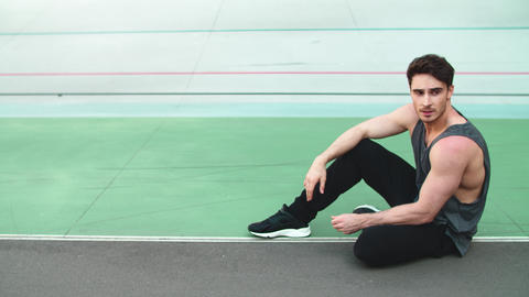 Tired runner sitting after workout on track. Exhausted man resting after workout Live Action