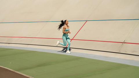 Sexy woman training on athletics track at stadium. Athlete woman sprinting Live Action