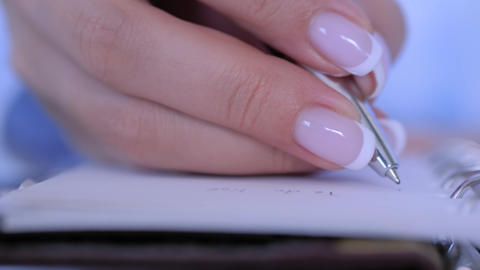 Slow motion: woman writing to do list in vintage notebook organizer Live Action