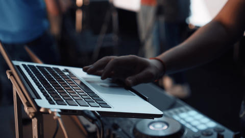 Footage of a professional DJ remote control before a concert on stage. DJ holds Live Action