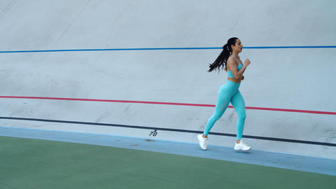 Sport woman running at sport stadium. Female runner running in sportswear Live Action