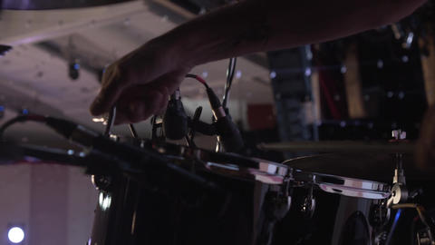 Close up of the hands of a drummer. A man adjusts equipment before a live Live Action