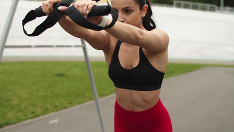 Sporty woman doing chest exercises on track. Sexy girl working out at stadium Live Action