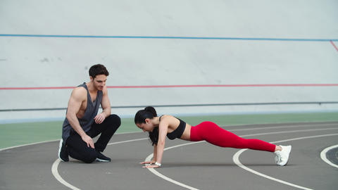 Woman doing push ups on sport stadium. Couple training together at sport stadium Live Action