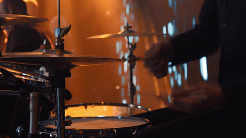 Close up of the hands of a drummer with a stick. The group performs on stage. A Live Action
