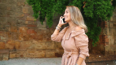 Relaxed woman walking with cellphone outdoor. Beautiful girl looking sightseeing Live Action