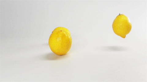 Few lemons falling down on white wet surface Live Action