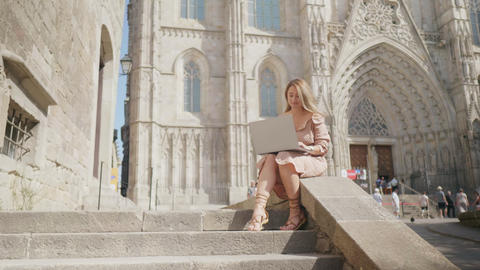 Pretty woman working laptop outdoor. Smiling businesswoman looking laptop screen Live Action