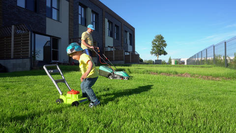 Father cutting lawn with lawn mower while son play with toy mower. Gimbal motion Live Action