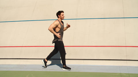 Athletic runner man running on athletics track. Fit man jogging on sport track Live Action