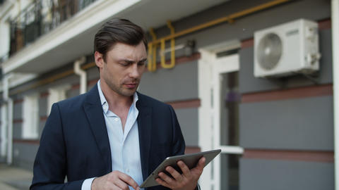 Closeup business man using tablet at street. Man working on touchpad outdoors Live Action