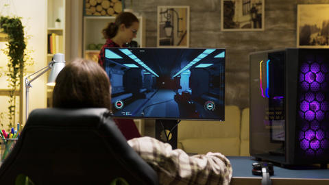 Back view of man sitting on gaming chair and playing games Live Action