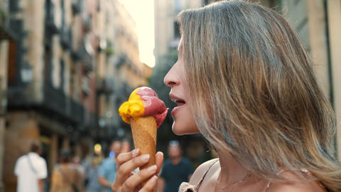 Close up cute woman eating gelato outdoor. Pretty girl licking ice cream Live Action