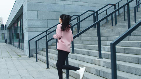 Fitness woman training run exercise on stairs. Sporty girl running down stairs Live Action