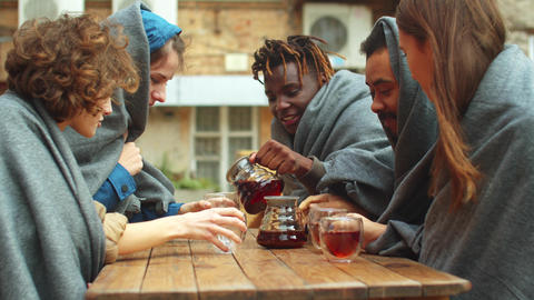 Group of friends in blankets sit outside the cafe and pour tea in cups Live Action