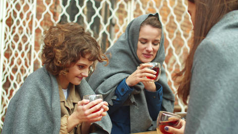 Girls in blankets sit outside the cafe, drink hot tea and talk Live Action