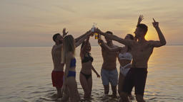 The six friends clink bottles on the water on a sunrise background. slow motion Live Action