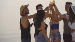 The happy friends clink bottles of beer on a beach. slow motion Live Action